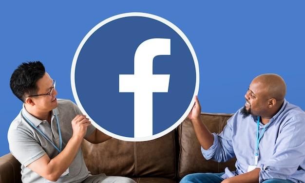 Facebookアイコンを表示している男性