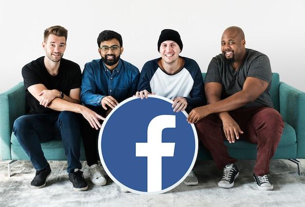 Facebookのアイコンを見せている男性