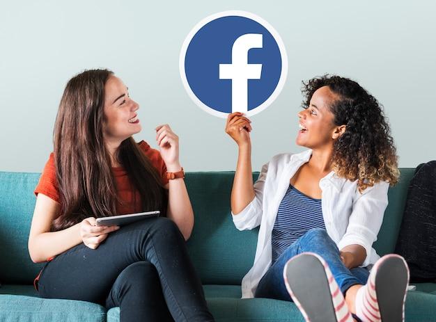 Facebookのアイコンを示す若い女性