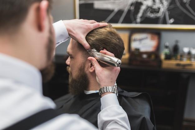 Faceless barber shaving hair of man