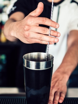 Faceless bartender mixing beverage with spoon