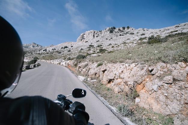 Faceless biker in stony countryside