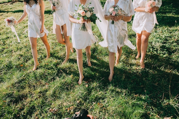 Faceless bridesmaids and brides dressed in satin robes with beautiful bouquets in their hands walk barefoot on the green grass in the garden. morning of the bride.