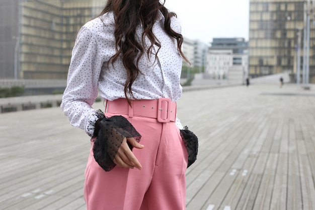 Faceless brunette female figure in white blouse and pink pants on street in paris