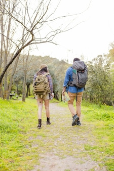 Faceless couple with backpacks