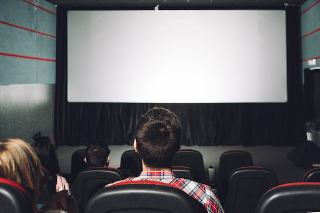 Faceless couples looking at cinema screen