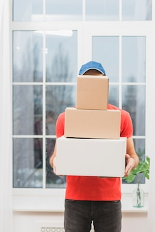 Faceless courier with stack of parcels