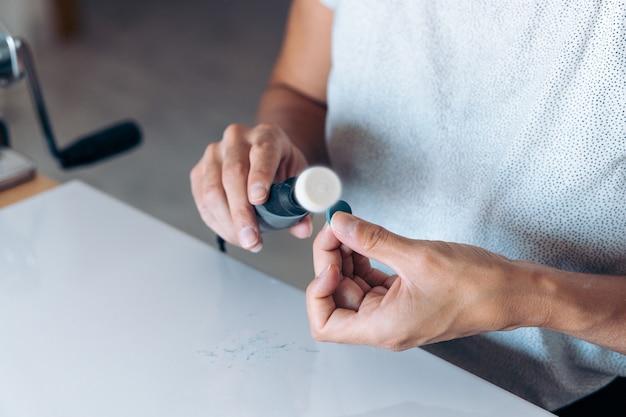 手作りの青いイヤリングをし、道具を使う顔のない職人。