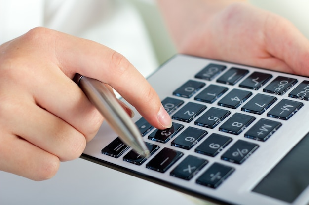 Faceless female considering on calculator
