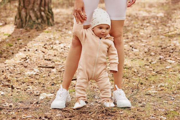아기가가는 것을 배우는 동안 얼굴없는 여성, 유아 딸 손을 잡고 숲에서 노는 가족