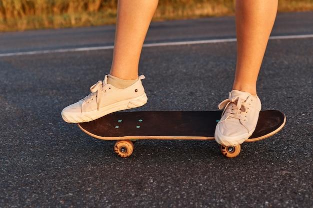 아스팔트 도로에서 롱보드를 타는 흰색 신발을 신은 얼굴 없는 여성, 알 수 없는 사람이 혼자 스케이트보드를 타고, 여자 다리가 스케이트보드를 탄다.