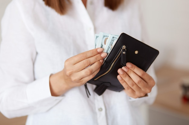 Faceless female wearing white casual style shirt, holding black wallet with money in hands, being ready to go shopping, saving money.