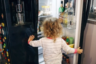 Faceless girl looking inside fridge