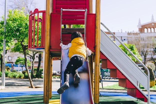 Faceless girl trying to climb slide