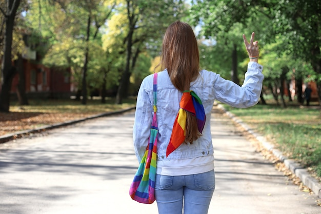 Faceless girl with rainbow scarf, bag and bracelet makes victory sign with her hand. pride concept