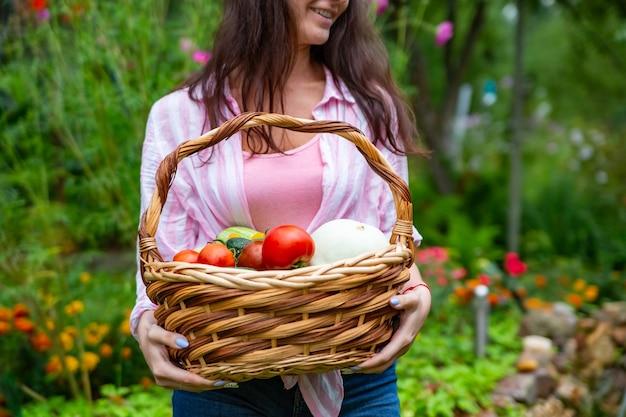 彼女の野菜の庭から野菜のバスケットを保持している顔のない幸せな笑顔の女性農家。顔をクローズアップしない