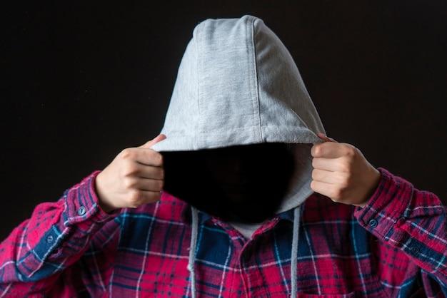얼굴 없는 시크릿 남자는 어두운 배경에 후드를 착용합니다. b
