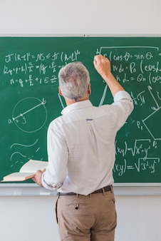 Faceless lecturer chalking formula on blackboard