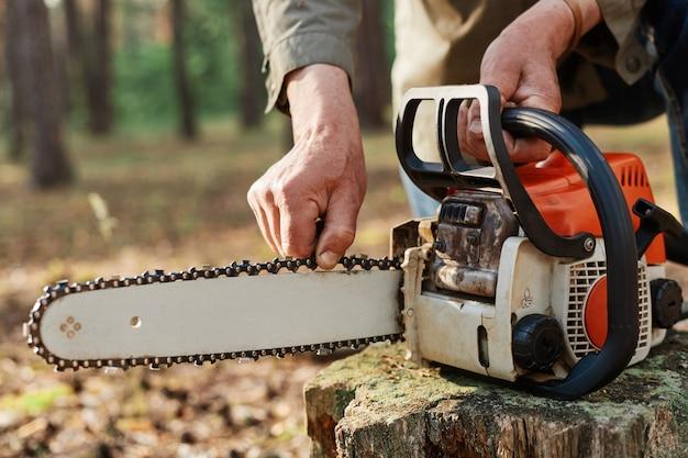 Faceless logger preparing chainsaw for work