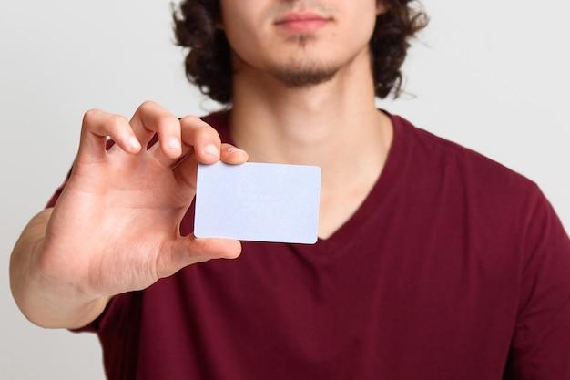 Безликий мужчина протягивает руку с пустой карточкой для вашего рекламного или рекламного текста, позирует на белой стене, человек, одетый в бордовую футболку. интернет-магазин, покупка, концепция технологии.