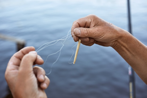 Faceless male untangles knot of fishing line over water, unknown person holding fishing line with bobber in hands, man catching fish with rod.