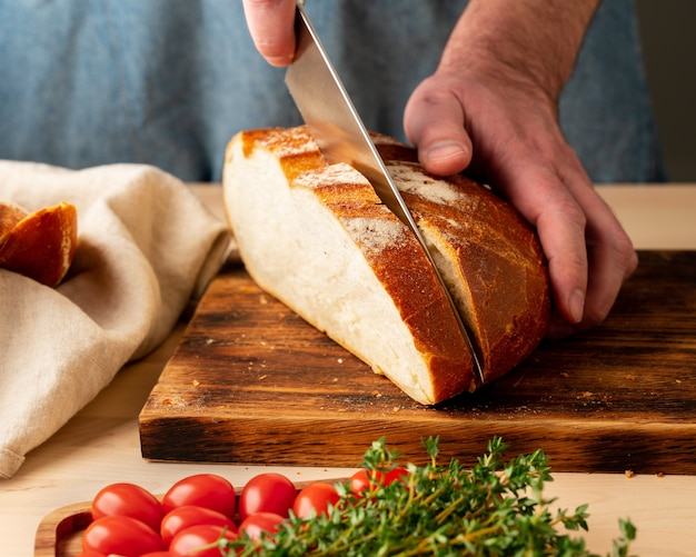 Faceless man cutting fresh home-baked crusty bread with large knife
