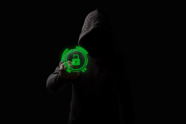 Faceless man in a hood touches the open lock hologram on a dark background