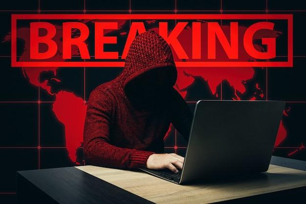 Безликий человек в халате с капюшоном сидит за столом с ноутбуком. концепция взлома и кражи пользовательских данных. добавлен текст breaking