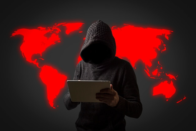 후드와 까마귀에 얼굴이없는 남자는 어두운 벽에 그의 손에 태블릿을 보유하고있다. 사용자 데이터 해킹의 개념. 해킹 된 잠금 장치, 신용 카드, 클라우드, 이메일, 비밀번호, 개인 파일