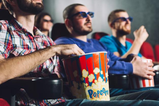 Uomini senza volto che guardano film al cinema