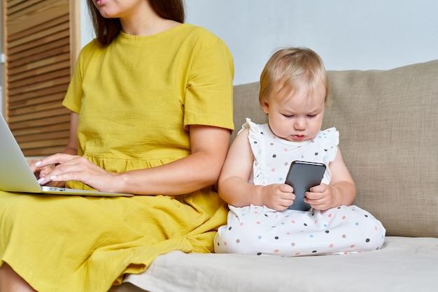 Безликая мама работает на компьютере, пока маленькая девочка использует мобильный телефон на диване