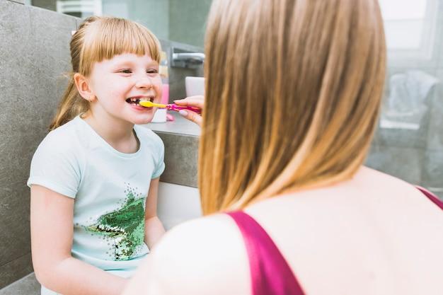 Faceless mother brushing teeth of daughter