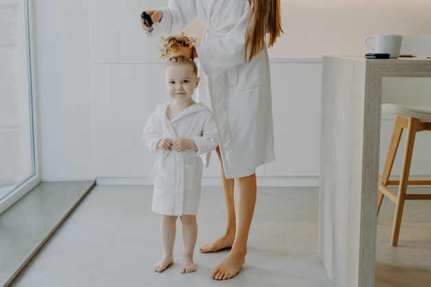 Faceless mother makes pony tail. cute little three year old girl in white bathrobe after taking shower poses near mom at home.