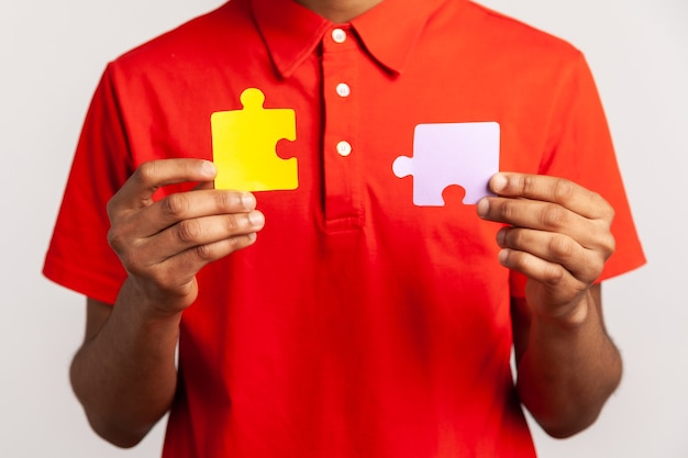 Faceless person holding two puzzle parts, connecting jigsaw pieces, symbol of unity and association