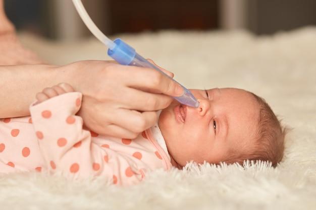 鼻の吸引を使用している顔のない人は、赤ちゃんから鼻水を吸い、ベッドに横たわっている乳児は、ふわふわの毛布の上でリラックスした、生まれたばかりの赤ちゃん、顔のないママに見えます。