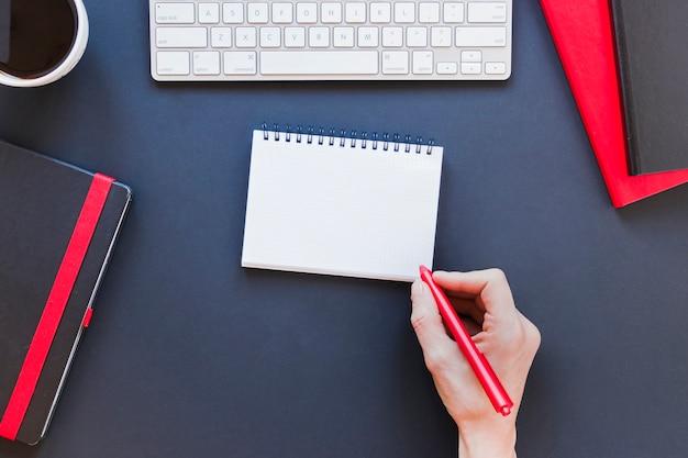 Persona senza volto che scrive in taccuino vicino alla tazza e alla tastiera di caffè