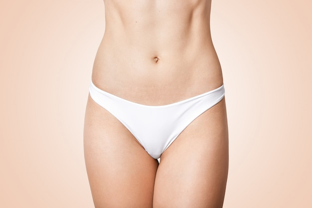 Faceless photo of woman in panties showing her perfect flat belly, lady has soft skin, wering white underwear, model posing isolated on beige. female health and intimate hygiene concept.