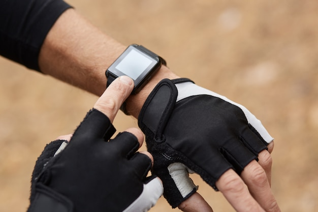 Faceless picture of man hand wearing smart watch and sporty gloves