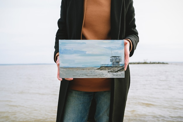 Faceless portrait of female artist standing on a beach, holding oil painting with a seashore