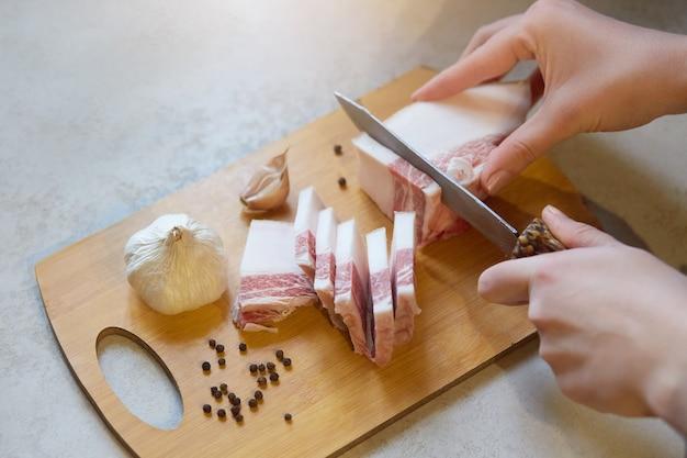Безликий портрет женщины, срезающей сало слоями мяса на деревянной разделочной доске среди чеснока, перца на белом столе, руки самок отрубы, леди, готовящая закуску для мужа.