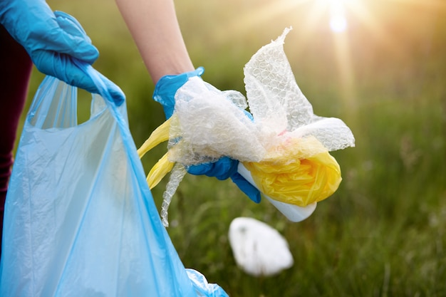 Faceless portrait of person picking up rubbish, wearing latex blue disposable glove, holding litter in hands, cleaning field, takes care of planet ecology.