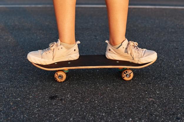 Ritratto senza volto di persona che indossa scarpe da ginnastica bianche in sella a skateboard su strada asfaltata, stile di vita sano.