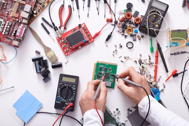 Faceless portrait of radioman testing electric current in circuit board of disassembled laptop using multimeter tool