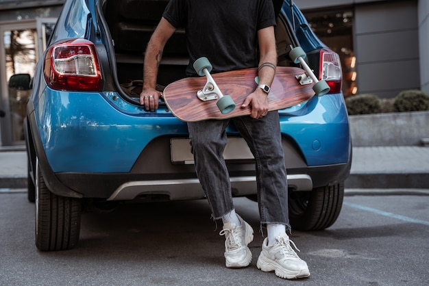Faceless portrait of young stylish man leaning on blue car trunk holding longboard wearing sneakers. city life concept. extreme sports concept, outdoors leisure concept. hipster concept. skateboarder.