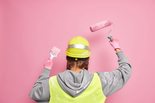 Faceless professional builder busy doing reconstruction of building stands back  uses equipment for painting walls wears protective hardhat and uniform poses against pink wall