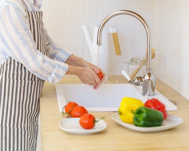 현대 부엌에서 요리하는 동안 샐러드 야채를 준비하는 앞치마에 익명의 고위 여자