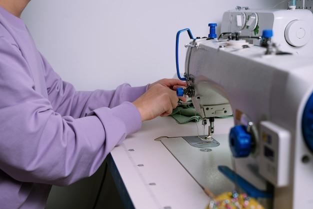 Безликий снимок женщины, работающей со швейной машиной в своей мастерской