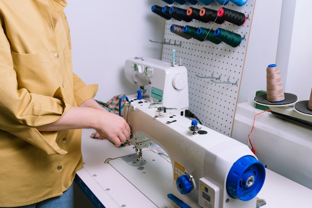 Faceless shot of woman adjusting sewing machine before work in sewing workshop
