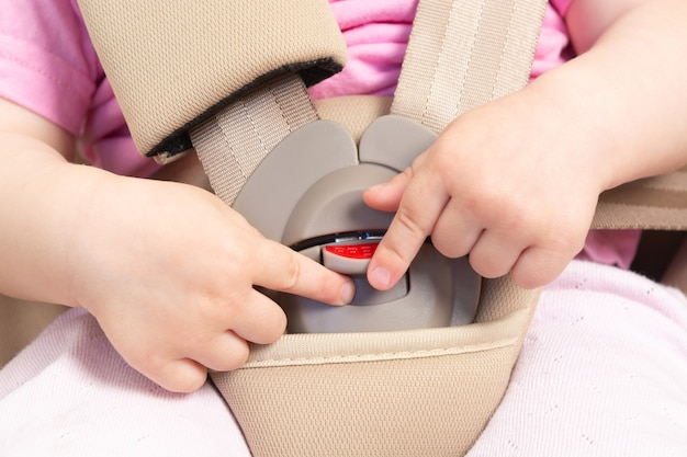 Безликий маленький ребенок сидит в специальном автокресле с ремнями безопасности