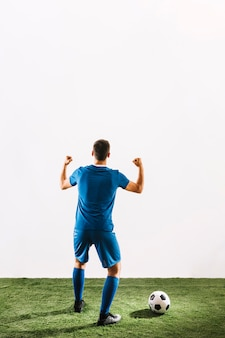 Faceless soccer player rejoicing over victory